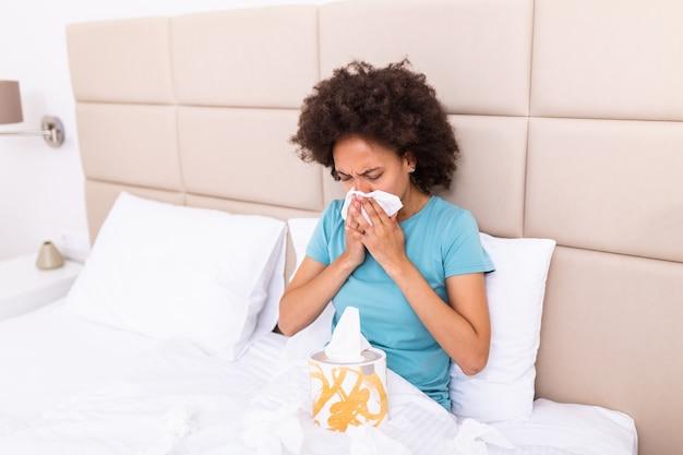 아픈 흑인 여자는 침대에 앉아 건강에 해로운 불고 코를 느낀다