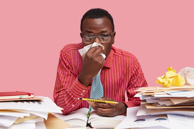 Sick black male worker has running nose, uses tissue, works in coworking space, holds spiral notepad with pencil, has to finish work, isolated over pink space