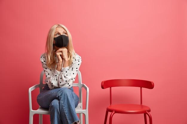 아픈 금발의 여자는 턱 아래에 손을 유지하고 집에서 코로나 바이러스에 대한 보호 마스크를 착용하고 집에서 실내 의자에 앉아 있습니다.
