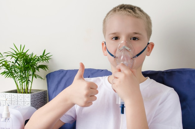 Sick boy breathing through inhaler mask and gesticulate thumbs up