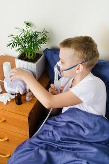 Sick boy breathing through nebulizer, inhaler for treatment prevention.