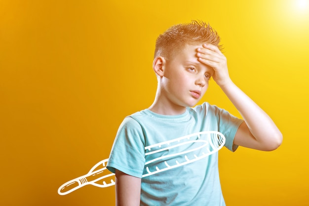Sick boy in light t-shirt measures the temperature of a thermometer on a colored