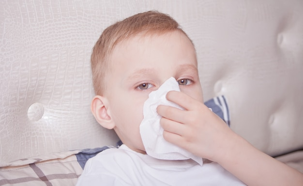 Sick boy lying in a bed and blowing her nose
