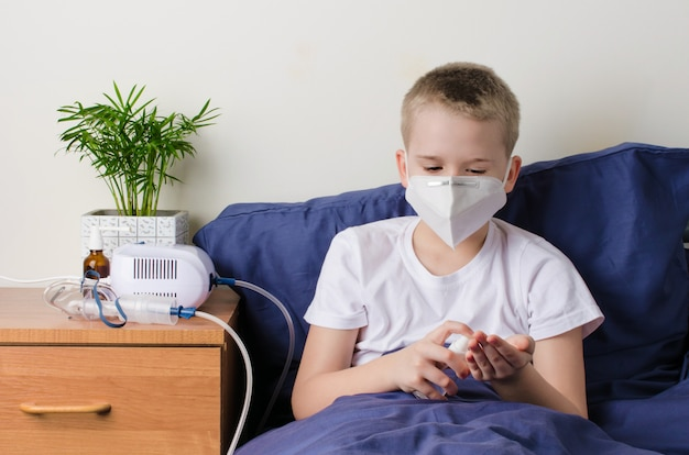 Sick boy in medical protective mask using hand sanitizer