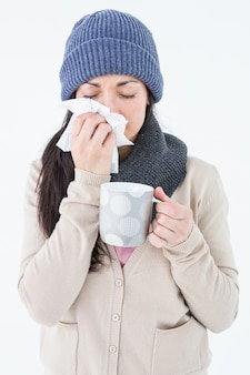 Sick brunette blowing her nose while holding a mug