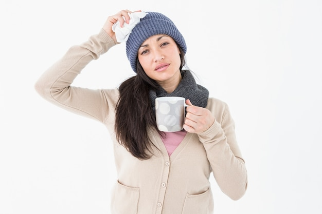 Sick brunette holding a mug and looking at the camera