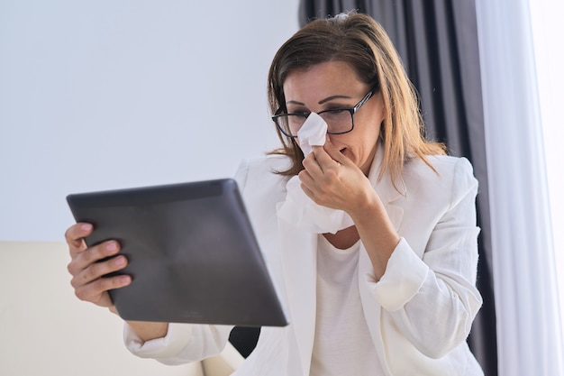 Sick business woman sneezing in handkerchief making video call, female looking at webcam of digital tablet talking to a doctor. woman making an important video conference while at home
