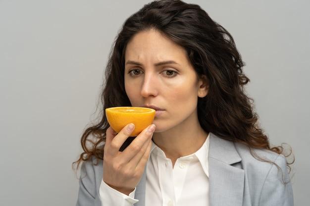 Sick business woman trying to sense smell of half fresh orange, has symptoms of covid-19, corona virus infection