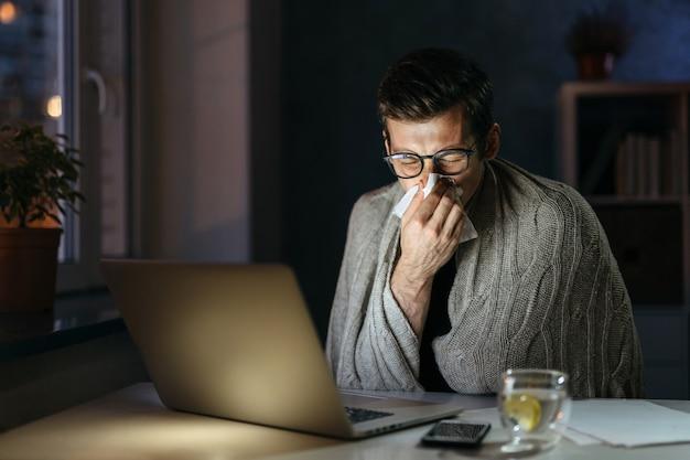 ホーム オフィスのコンピューターで作業中に鼻をかむ病気のビジネスマン