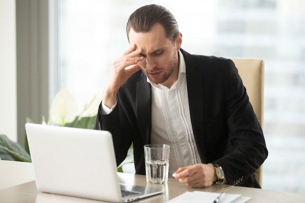 Sick businessman having severe headache