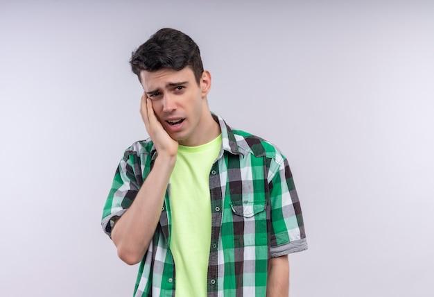 Ragazzo giovane caucasico malato che indossa la camicia verde mise la mano sul dente dolorante su fondo bianco isolato