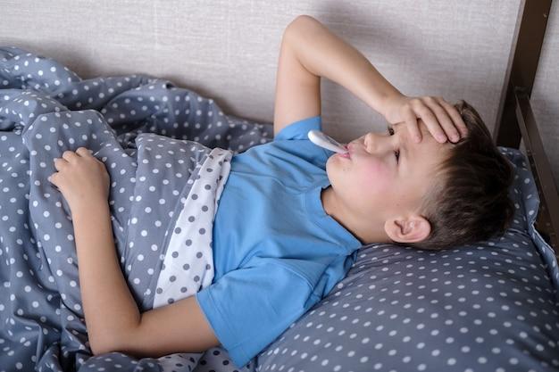 Больной ребенок мальчик лежит в постели с термометром во рту и касается его лба