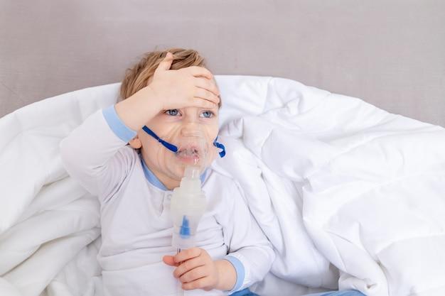 흡입기를 가진 아픈 아이 소년은 집에서 목구멍을 치료하고 온도를 측정합니다.