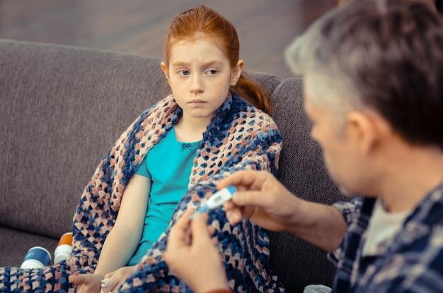 아픈 아이. 건강을 걱정하면서 아빠를 바라 보는 우울한 소녀
