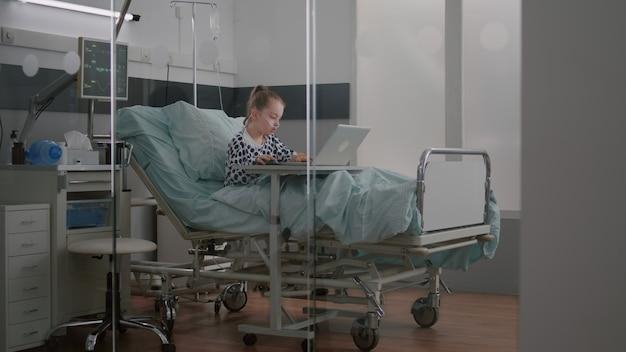 Bambino malato che si rilassa a letto giocando ai videogiochi dei cartoni animati sul computer portatile durante la visita medica...