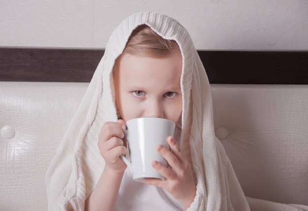 The sick child sitting in a bed and holds a cup of tea