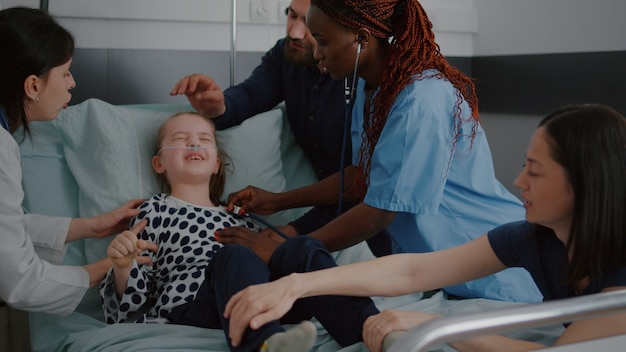 Sick child struggle while african american nurse trying to check heartbeat pulse