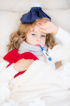 Sick child with fever and hot water bottle at home