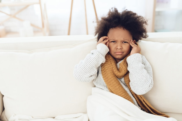 Sick child with flu in scarf sitting on couch at home.