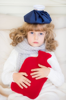 Sick child with hot water bottle in bed