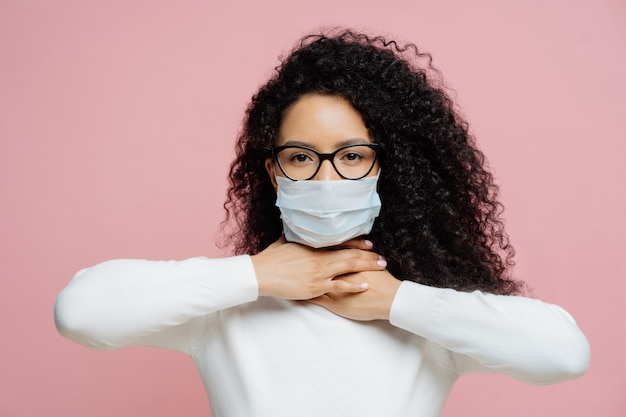 Sick curly haired woman touches neck, suffers from suffocation and shortage of breathing, wears medical mask to avoid virus infection