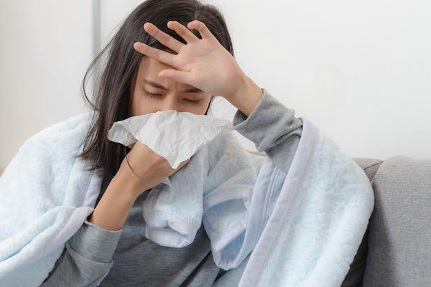 집에서 아픈 하루. 아시아 여자는 콧물과 감기에 걸렸다.