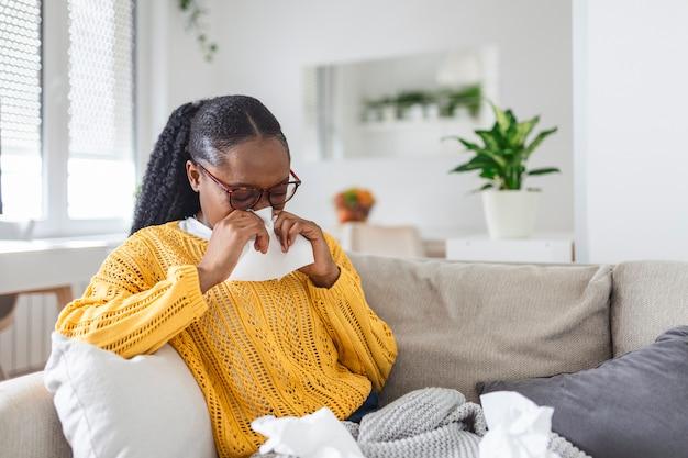 自宅で病欠。若い女性は鼻水と風邪をひいています。咳。風邪やインフルエンザの病気にかかった美しい若い女性のクローズアップ。コロナウイルス、covid19症状を持つ不健康な女性の肖像画