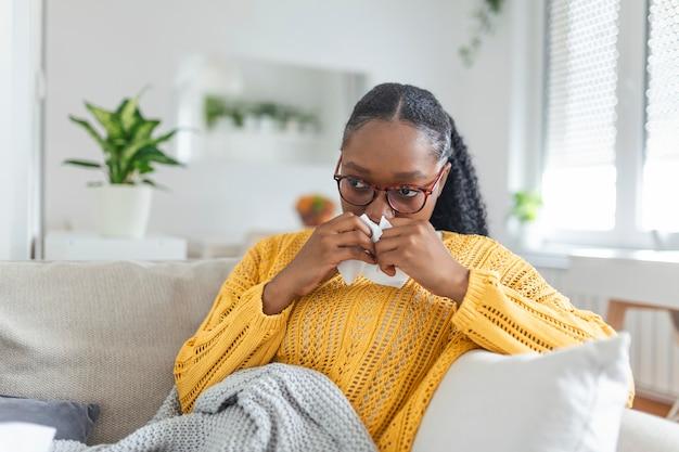 自宅で病欠。若い女性は、鼻水と風邪をひいています。咳。風邪やインフルエンザの病気にかかった美しい若い女性のクローズアップ。コロナウイルス、covid19症状を持つ不健康な女性の肖像画