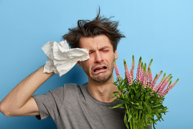 Больной, удрученный молодой человек трет глаза платком, у него аллергия на сезонные цветы или растения, он несчастно плачет, устал бороться с аллергенами, нуждается в хорошем лечении, стоит в помещении