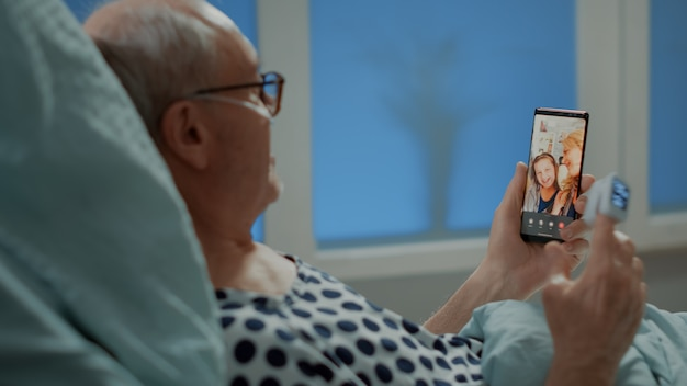 Paziente anziano malato che parla in videochiamata con la famiglia nel reparto ospedaliero