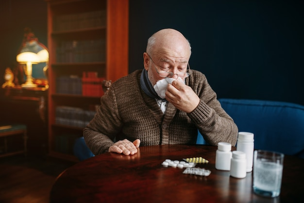 Sick elderly man blows his nose in a handkerchief in home office, age-related diseases