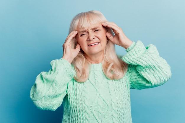 Sick elderly woman lady put hand head suffer headache isolated on blue background