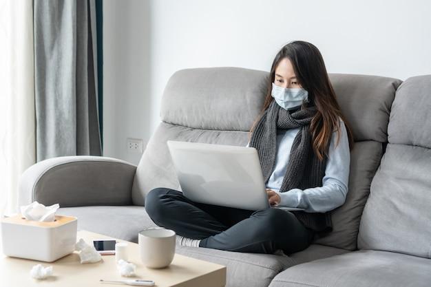 自宅のラップトップで作業している発熱と頭痛に苦しんでいるサージカルマスクを身に着けている病気の従業員。コロナウイルスのパンデミックの概念の間、在宅勤務、医療、自宅検疫、または隔離。