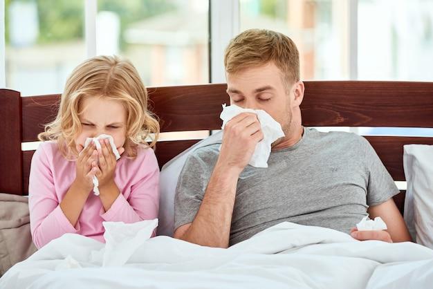 독감이나 감기에 걸린 아픈 가족 아버지와 딸이 누워서 코 닦기