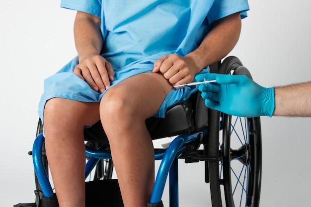 Больная пациентка получает инъекцию в колено врачом