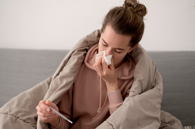 Sick female person blowing her nose