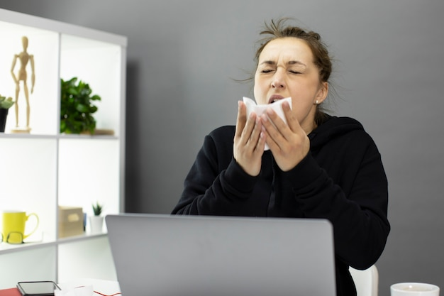 Sick freelancer sitting in home office sneezes covering her mouth with napkin