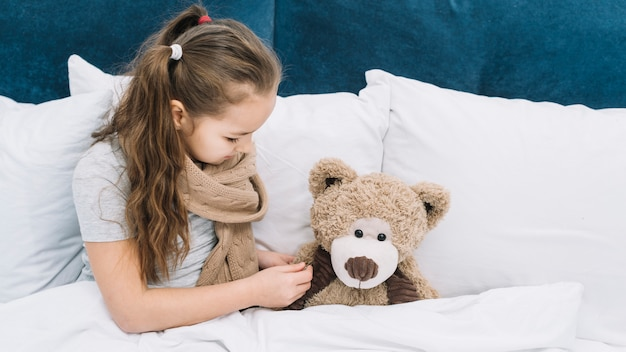 Sick girl checking the temperature of teddy bear with thermometer