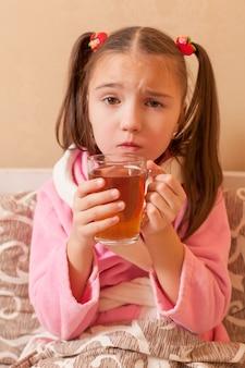 Sick girl has drink hot tea