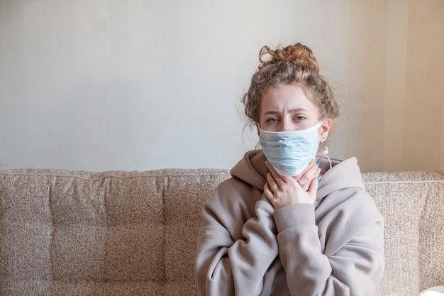 防護マスクで病気の女の子。コロナウイルスの概念。テキストスペース