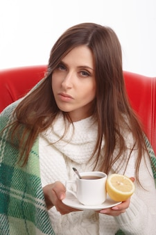 Sick girl posing with a hot drink and a lemon