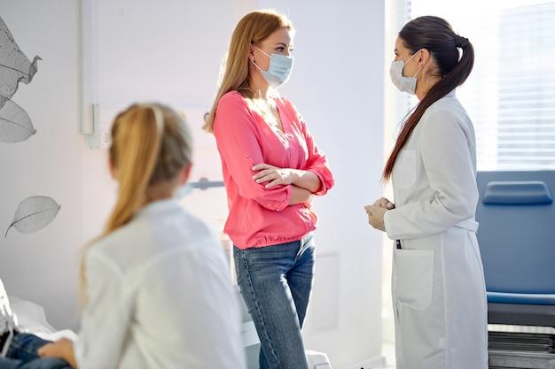 病気の女の子は、病院で医者と話している母親を見て、解決策、治療法、医療用マスクを待っています。コロナウイルス、covid-19。大人に焦点を当てる