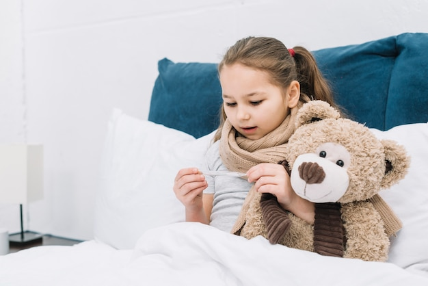Sick girl sitting on bed with teddy bear looking at thermometer