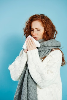 Больная девочка чихает и вытирает нос