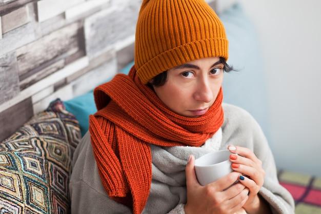 スカーフと帽子でソファーに座っていたお茶のカップを持つ病気の女の子。家に。