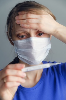 A sick girl with a fever in a disposable medical mask looks at the thermometer.