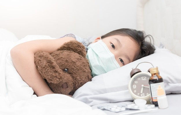Sick girl with hygienic mask laying on bed, healthy concept