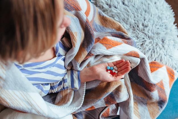 一握りの薬が入った毛布にくるまって病気の女の子