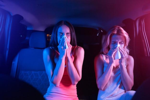 아픈 소녀는 차에 앉아 마른 냅킨을 불고 있습니다.