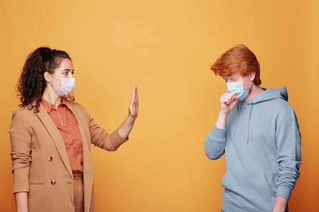 若い女性の前で咳をしている保護マスクの病人は、感染症から身を守るために喜んで停止ジェスチャーを示しています